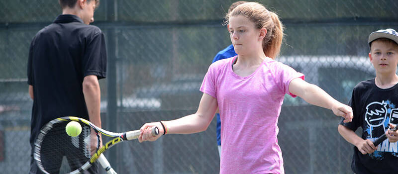 Girl hitting tennis ball with pink shirt on