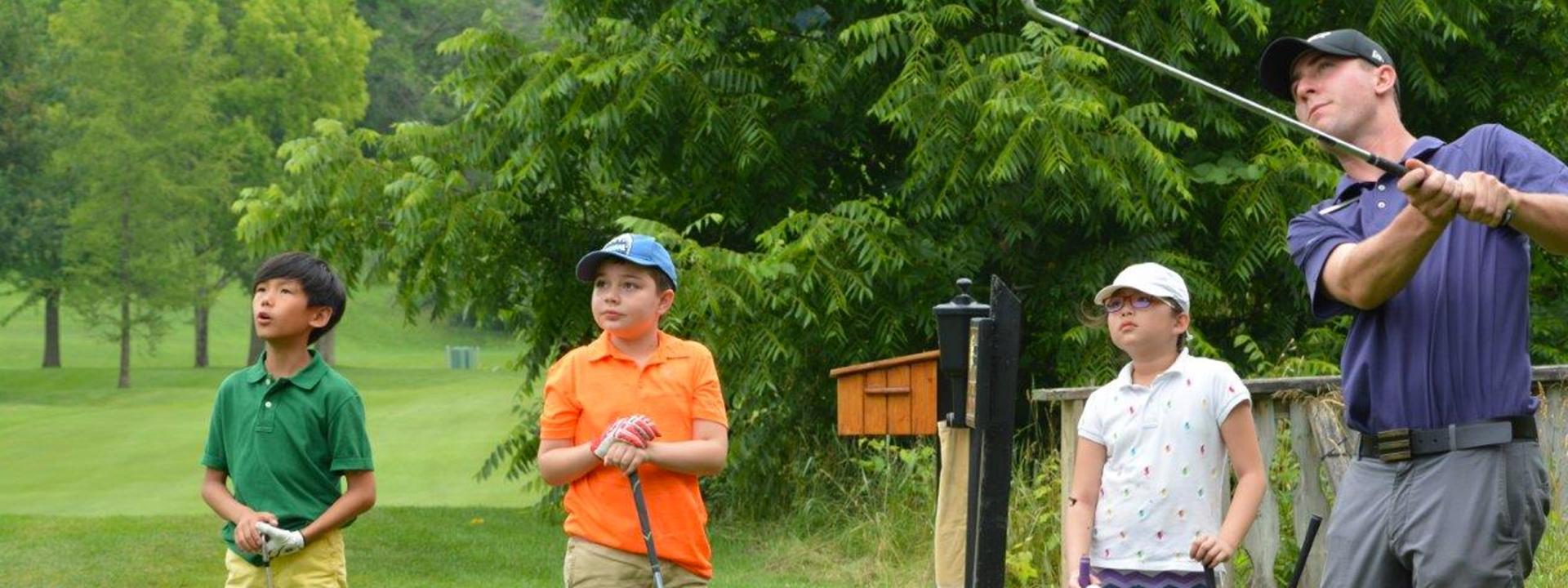 three kids and a man golfing
