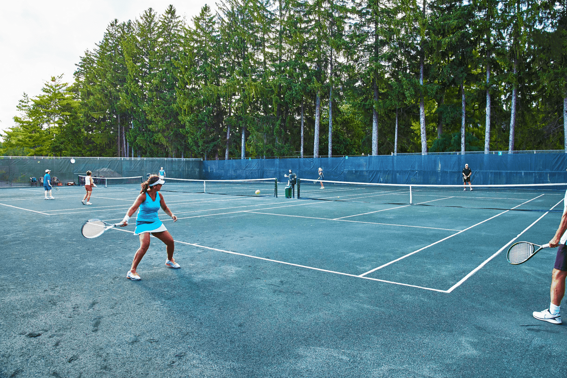 A lady playing tennis at the Thornhill ground on a large tennis court with other players